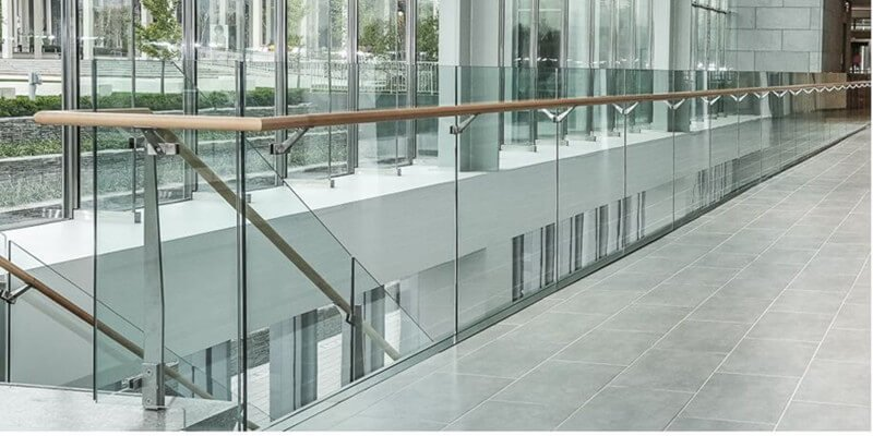interior commercial glass railing with base shoe and wood handrail for office building